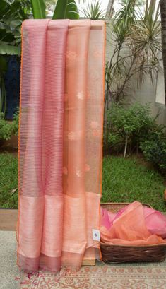 This elegant kora sari is in cantaloupe orange and punch pink. The sari is a half and half with beautiful floral bhuttas woven on side in salt white and gold zari. The other side has regular stripe Indian Dresses, Indian Outfits, Indian Clothes, Simple Sarees, Elegant Saree, Work Sarees, Cantaloupe, Punch, Salt