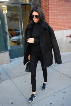 Kendall Jenner wears a black shearling coat, mock neck top, skinny jeans, and Nike sneakers on Nov. 8, 2015 in New York City.