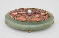 Bell push Oval bowenite two-coloured gold bell-push with convex oval top enamelled with guilloché salmon pink sunburst design and mounted with gold bead and reed borders and entwined green gold laurel garland. Mecca stone push surrounded by diamonds and sitting atop gold arrow. Unmarked