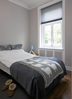 Soverommet er lett og luftig, med duse toner og god takhøyde. Et morsomt ullpledd med bilder av sauer ligger på sengen.