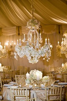 Chandeliers covered with white flowers hang above each table in a tented wedding.