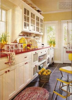 creamy retro look cabinets, fresh red & yellow decor, love the dark gray/black slate look floor tiles, the glass fronted upper cabinets, the tin look fronted lower cabinets, the open shelves below the upper cabinets - the red counter top & hardware could just as easily be black or charcoal