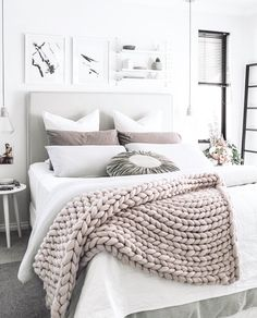 way to style the headboard: three matching size paintings. pillow arrangement ideas too.