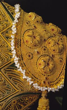 The 'traje de luces' or suit of lights assimilated 18th C  fashion of the Bourbon court for decorative embellishment, it became blended with the stylized characteristics of Islamic patterns, a reminder of Spain's 8th and 9th C Moorish past, and more contemporary fashions of floral and Christian iconography.  The eventual use of gold thread and bullion came later, around the beginning of the 19th century and can be documented in images painted by Goya.