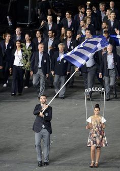 London 2012 Opening Ceremony - Greece's flag bearer Alexandros Nikolaidis holds the national flag as he leads the contingent in the athletes parade during the opening ceremony of the London 2012 Olympic Games at the Olympic Stadium July 27, 2012. REUTERS/Dylan Martinez