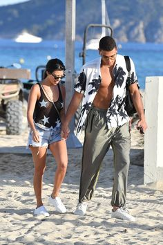 Feeling good: Her young boyfriend wore a white short-sleeved button down and green athletic trousers