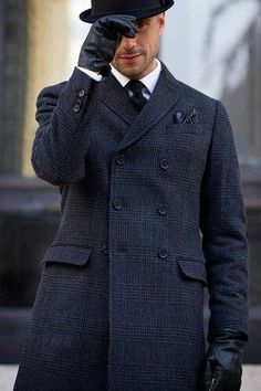 Opt for a navy plaid overcoat and a white oxford shirt for a sharp classy look.  Shop this look for $224:  http://lookastic.com/men/looks/hat-gloves-dress-shirt-tie-overcoat/7675  — Black Wool Hat  — Black Leather Gloves  — White Dress Shirt  — Black Tie  — Navy Plaid Overcoat