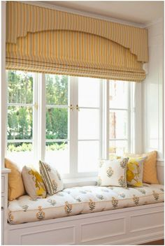 beautiful layered treatment. Cornice board & roman shade with compatible fabrics on the window seat!