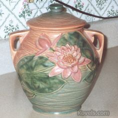 "Roseville Cooke Jar. Roseville's Water Lily pattern was introduced in 1943. Over 50 different pieces were made in the pattern. Background colors were blue, brown or pink. The number ""8"" in the mark refers to the jar's height, 8 inches. Pieces in Water Lily are easy to find, but cookie jars are one of the items collectors look for."