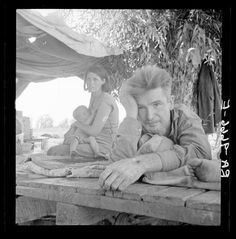 """Mother breastfeeding baby. 1930's Great Depression """"Drought refugees from Oklahoma camping by the roadside. They hope to work in the cotton fields. There are seven in family. Blythe, California. LC-USF34- 009666-E.  Lange, Dorothea, photographer"""""""