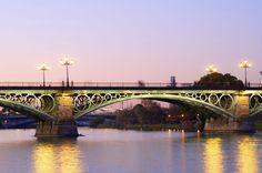 """Nada tiene que envidiarle a los puentes más conocidos de Europa. Une el centro de Sevilla con el mítico barrio de Triana, de ahí su nombre, aunque en realidad se llama puente de Isabel II. En uno de los extremos, el de la parte de Triana, hay una pequeña capilla muy querida por todos los sevillanos, la capilla del Carmen o """"el mechero"""", como les gusta llamarla. Y es que este puente une dos Sevillas muy diferentes: una moderna y señorial y otra con mucho duende y pasión."""