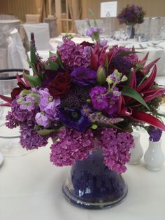 Vase centrepiece of deep purple and plum stocks, lilac, lisianthus, Black Bacarra roses and burgundy lilies. Taken from a recent wedding at Carlton Mitre Hotel, Surrey.  For more wedding flowers ideas please visit http://www.thefineflowerscompany.co.uk/weddings/html