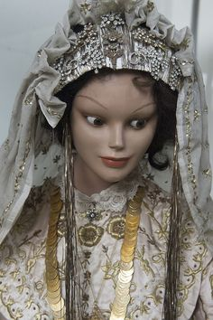 Exuberant bridal headgear.  Urban style, from Bursa, 1900-1950. The headscarf is adorned with 'telkırma' (or: Bartın işi = work from Bartın): folding thin silver slat into the fabric, creating two identical sides.  The silver glitter festoons that hang down are a local Bursa-City addition, exclusively used for brides.  It has been adopted in villages of the province too.  Photographer/copyright: Dick Osseman. To see more of the Bursa Etnografya Müzesi…