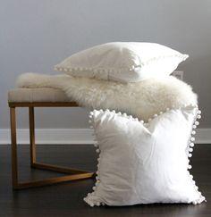 Designer curated custom pillow with white fabric with white pom pom trim