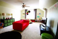 Bold and colorful playroom - love the storage units and red pop of color in the couch!