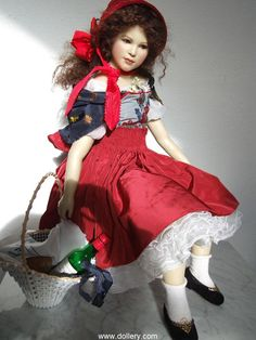 """""""Little Red Riding Hood"""" OOAK by Hanna Goetz.  One-of-a-Kind, High-Fired Clay w/Wax Body - Strong Moveable Skelton w/Soft Stuffing Body, Green Mouth Blown Glass Eyes, Reddish Brown Human Hair, 28.3""""   Seated with Hat"""