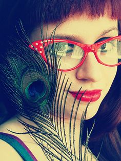 Red cat-eye glasses and peacock feather