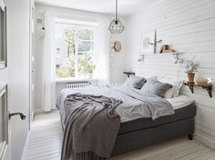 Bedroom with white wooden planks wall