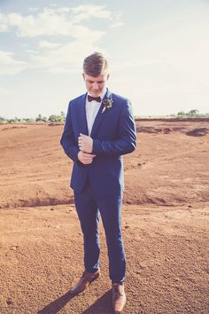 Groom wearing blue suit with burgundy bow tie and brown shoes for desert wedding | Renee Lee