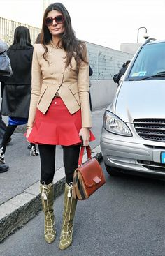 Giovanna Battaglia wears a leather jacket, red miniskirt, tights, knee-high boots, and a top-handle bag