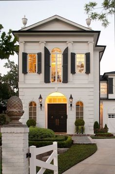 Now THIS is what I call a house: French home exterior with Greek columns and black shutters. Black front entrance door with arched windows and iron lanterns flanking grand entrance.