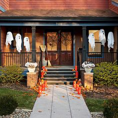 Go all-out on your outdoor Halloween decorating. On the stairs, welcome guests with tall lanterns wrapped in cardstock cut with faces, and situate among small pumpkins and gourds. Accent pillars with spooky planters, hang ghosts from the porch, and use tape to create black spiderwebs on your doors. As a final touch, wrap spare brooms with electrical tape for a cheap door-side accent./