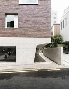 Top-heavy office and apartment block features brick top and concrete base