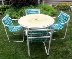 """Very Nice Vintage Samsonite Table  Chairs 1967  Hard to Find Sunrest line-Sooo retro  Table top is a powdered-marble swirl pattern in a   muted pastel yellow/green - very 60's  Top lifts off base for ease of moving. Early style for umbrella hole.  Frames are a white powder-coated aluminum-original  All (4) chairs and table are structurally sound  The slatted """"Air Cushion"""" pads are blue  green vinyl and original."""