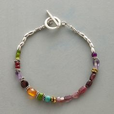 DOMINION BRACELET--Pink tourmalines reign among multicolored gems of amethyst, turquoise, carnelian, garnet and ruby. With brass and sterling silver beads