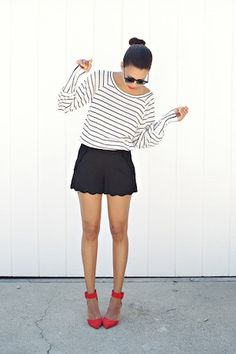 scalloped shorts and bright red shoes.