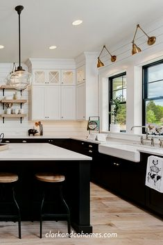 Black windows sit below antique brass sconces that highlight the white apron front farm sink that is both stylish and functional. Kitchen Redo, Home Decor Kitchen, Interior Design Kitchen, New Kitchen, Kitchen Makeovers, Kitchen Renovations, Modern Farmhouse Kitchens, Black Kitchens, Home Kitchens