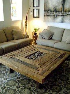 Esta mesa de centro ha sido fabricada reciclando listones de madera a los que han dado acabado rústico y natural, aún más con la inclusión de piedras de canto rodado en la parte central.