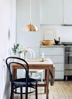 small kitchen with copper pendant lamp and black and white bentwood chairs. / sfgirlbybay