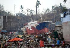 Ships lie next to destroyed houses after being swept ashore at the height of Typhoon Haiyan in Tacloban city, on November 14, 2013