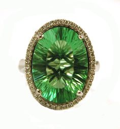 GREEN FLUORITE AND DIAMOND RING, 14k white gold with round-cut diamonds set around an oval, mixed-cut green fluorite weighing approximately 13.70 cts. Ring size: 7. Estimated to sell between $600-800. To be sold as lot 0814-0105.