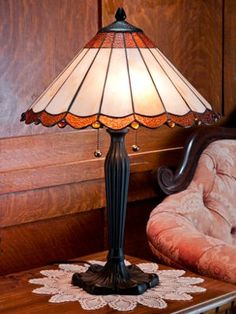 Simple yet elegant stained-glass table lamp captures the famed Tiffany style with a hand-cut glass shade