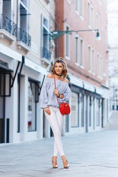 Showing off playful streetwear, Larisa Costea accessorizes slim white jeans with a quilted redcross-body, nude pumps and plenty of jewellery. Her adorable off-the-shoulder peasant top is balanced by two slim black chokers. Shirt: Chicwish, Jeans:...
