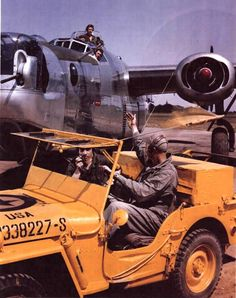 Brightly painted Willys MB Jeep leading B-24J aircraft at an unknown USAAF Air Field.