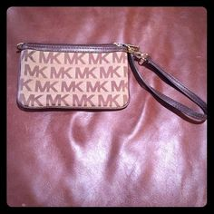 BUY ONE, GET ONE FREE SALE - Michael Kors Wristlet Signature Brown Logo. Inside pocket. Great condition. Very little wear. No stains or fraying. Some scratches on hardware. Very minor wear on corners and top edge. (Dollar is for reference only ) Will take wear into account when entertaining offers. Michael Kors Bags Clutches & Wristlets
