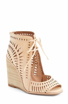 Eye-catching geometric cutouts call attention to an earthy, vintage-cool peep-toe sandal set on a stacked wedge.