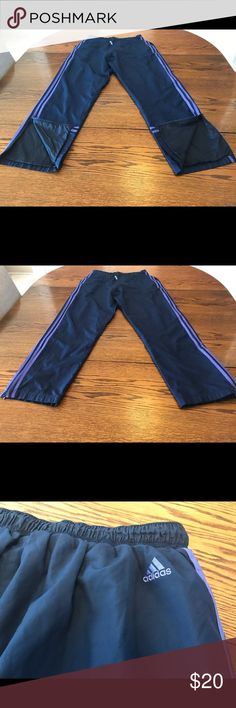 Adiddas nylon jogging pants. Blue/ purple size L Adiddas nylon jogging pants. Blue/ purple size  L. polyester. These gorgeous trendy pants are dark blue with purple stripes down the sides. They have zippered hidden pocket on one side along with two regular pockets. The bottoms of the legs have a zippered vent opening. Inseam 29. Slight stretching of the thread in the crotch which is easy to repair. Very nice nylon pants adidas Pants Track Pants & Joggers