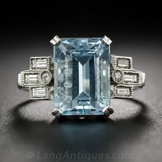 Aquamarine and Baguette Diamond Ring. A refreshing cool blue emerald-cut Aquamarine glistens between geometric arrays of straight baguette diamonds (plus one small round diamond) in this late-Art Deco bauble, crafted in platinum and dating from the middle of the last century
