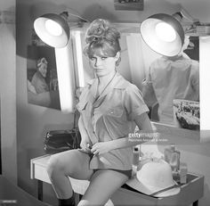 French actress Brigitte Bardot sitting and buttoning up her blouse in a scene from the film 'Only for Love' directed by Roger Vadim. Behind her, two lights and a mirror. 1961