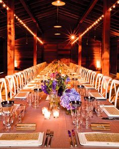 Fifty guests sit at one long table set inside a rustic barn.