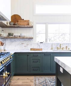 Amber Interiors is another perpetual favorite, and we love this combination of wood and marble with the dark green cabinets! Image via Amber Interiors. Green Kitchen Cabinets, Kitchen Cabinet Colors, Painting Kitchen Cabinets, New Kitchen, Kitchen Dining, Kitchen Decor, Kitchen Ideas, Blue Green Kitchen, Stylish Kitchen
