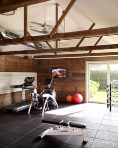 """Gym. ROBERT STILIN /INTERIOR DESIGNER """"I like to add warmth to a home workout room by mounting framed mirrors instead of the frame-less ones you find in most gyms. In an old barn, we preserved the original walls and beams to soften the environment. When choosing equipment, I ask my client about his or her needs, then consult a trainer and work with a company like Gym Source""""; gymsource.com."""