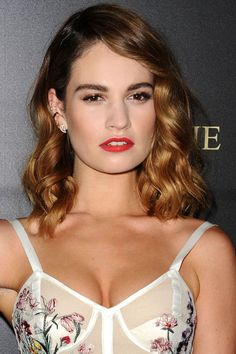 """Who: Lily James What: Soft Waves and Red Hot Lips How-To: Sisters Ashley and Jenn Streicher created soft waves and an orange-red lip for the actress, who wore a lingerie-inspired McQueen dress to the premiere of Pride and Prejudice and Zombies last night. """"We wanted the look to convey accidental sexiness,"""" said Jenn, who decided on a hotter shade of red for a more modern, youthful feel. Ashley curled two-inch sections of hair around the head, then used a vent brush to """"break up and stretch…"""