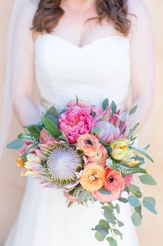 This stunning handmade bouquet features pink peonies, yellow garden roses, succulents, and king protea to tie together this colorful outdoor destination wedding at The Royal Palms in Scottsdale, Arizona. Bride and groom portraits photographed by wedding photographers Amy and Jordan Demos, designed by Some Like it Classic and floral by Petal Pusher #outdoorwedding