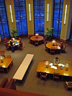 Library Setting: vertical lights on the walls and wooden study tables/chairs each with it's own small lamp