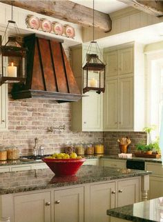 Farm house kitchen with a copper vent hood. This is what I want. Brick back splash, love the cabinets, the rustic exposed beams and the hanging lanterns.